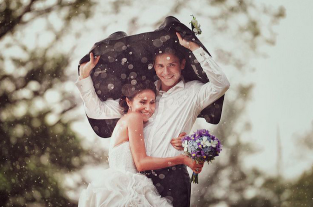 groom holding jacket over himself and bride in rain