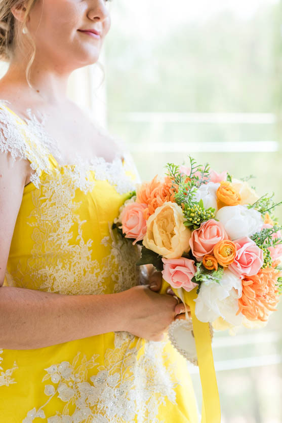 bride in yellow dress holding flowers